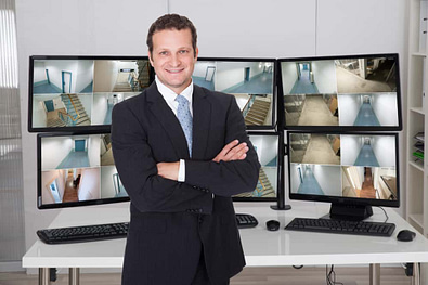 Portrait of confident manager standing arms crossed against monitors at office