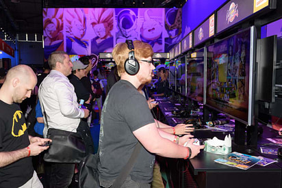 Trade fair visitors playing the game dragonball fighter z at Gamescom