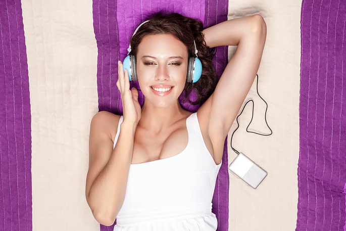 Young woman listening to music through MP3 player using closed back headphones while lying on picnic blanket