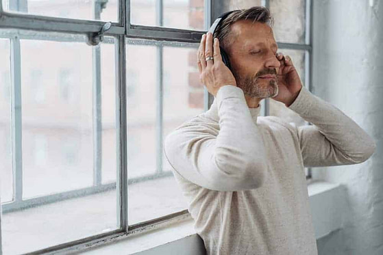 Attractive middle-aged man listening to music