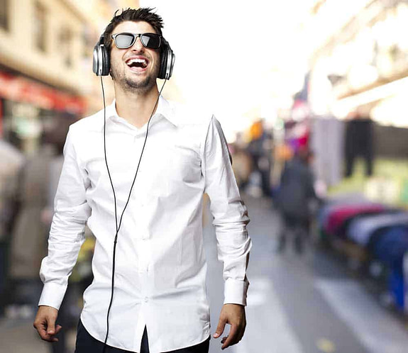 portrait of young man laughing and listening to music at street