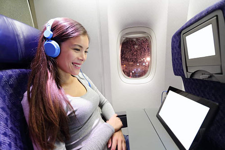 Plane passenger in airplane using tablet computer