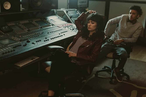 Young depressed musicians sitting in chairs at recording studio