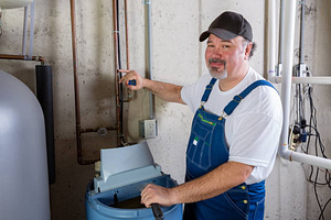 Friendly smiling workman in dungarees installing or working on a water softener in a utility room turning to smile at the camera