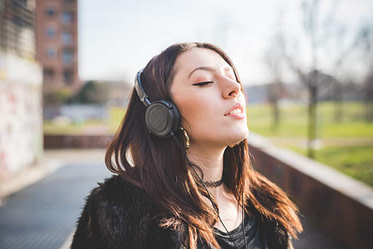 Young beautiful indie woman with septum piercing outdoor in the city listening music with headphones relaxing with eyes closed - music, relaxing, carefree