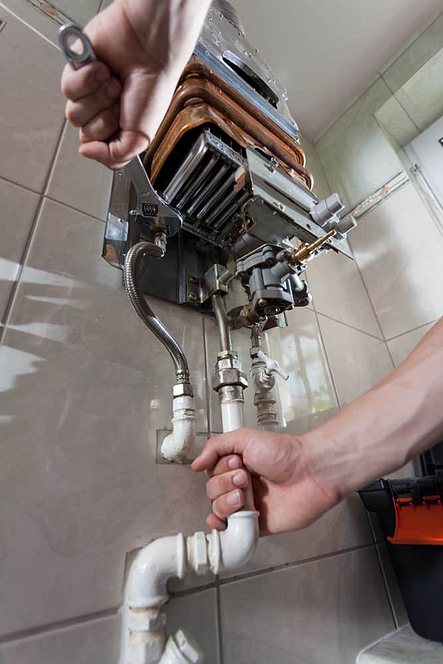 Plumber mending a gas water heater with a wrench