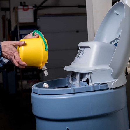 Salt pellets are added to the reservoir of a water softener