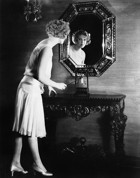 Woman looking into a mirror about to ring a bell