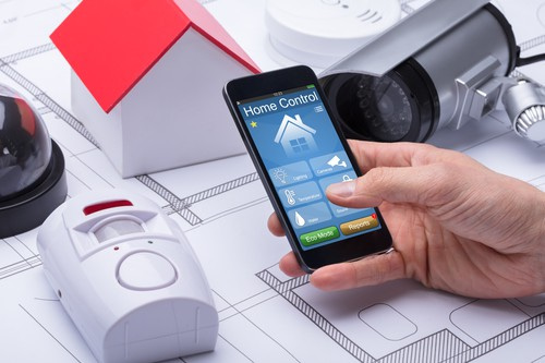 Architect's Hand Using Home Control System On Mobile Phone