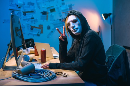 Female hacker in mask showing v sign at workplace