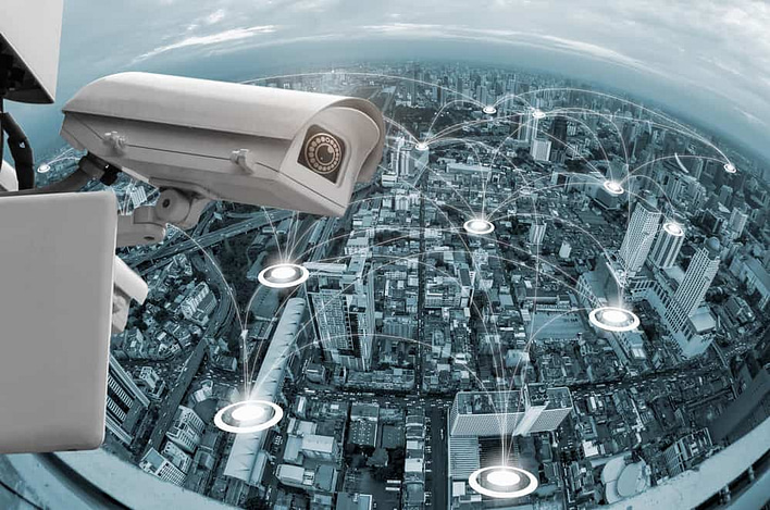 Monitoring security camera on backdrop of the blue blur building with network