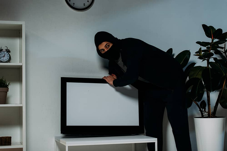 Suspicious robber in mask stealing flat-screen tv with blank screen