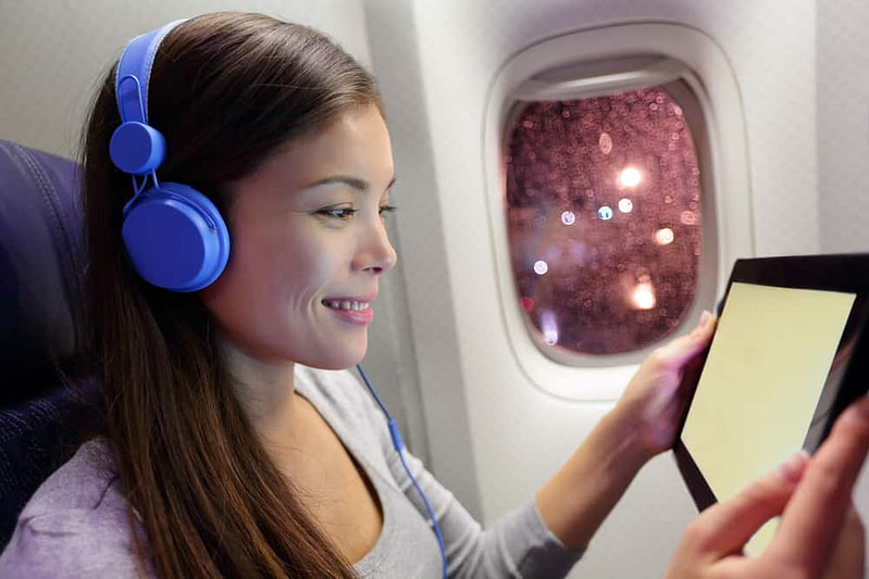 Passenger in airplane using tablet computer. Woman in plane cabin using smart device listening to music on headphones.