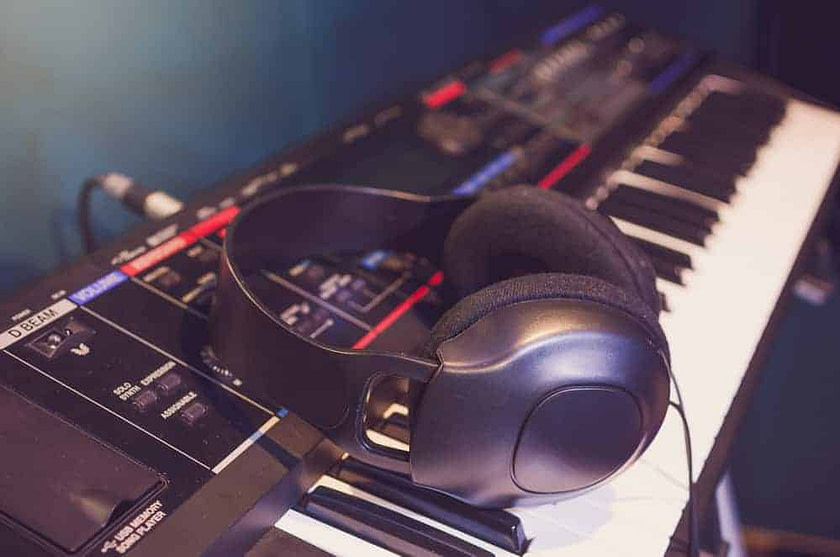 Close up of headphone on keyboard in music studio room, music in